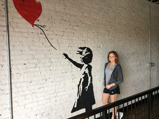 Artist Andrea Ehrhardt painted the girl with the balloon. She also painted the design that once was on the front door of the building 108 Park Central Square.