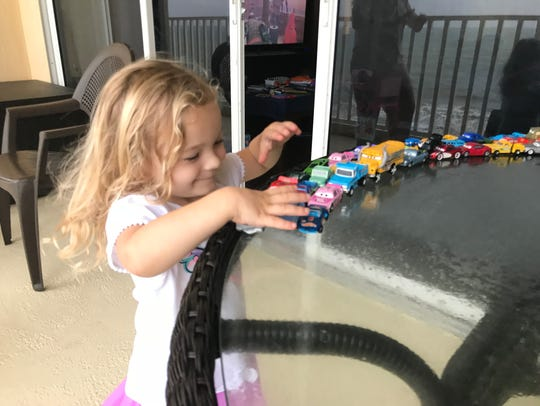 Isabella lines up her toy cars as if they were in traffic