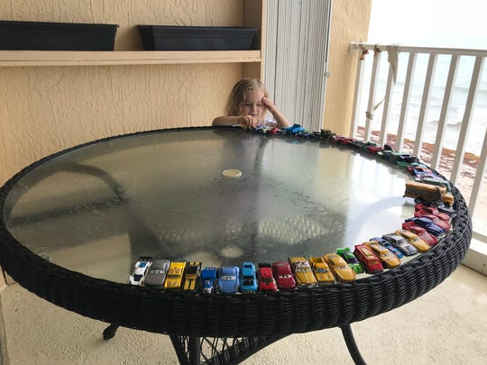 Isabella sorts her toy cars to all be facing outward