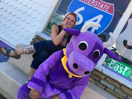 "Purple Cow owner Becky Kincaid with Matt Thomas as the ""Purple Cow."""