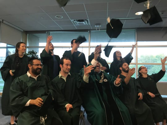 The 10 graduates throw their hats into the air at Thursday's alternative commencement ceremony with RCC President Michael Baston.