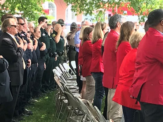 Local emergency personnel salute the flag during the national anthem during the Flags of Freedom ceremony last Tuesday.