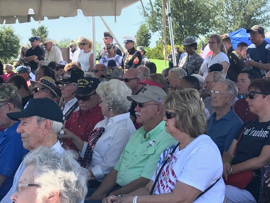 Attendees of the annual Memorial Day ceremony at Texas State Veterans Cemetery at Abilene listen to a speaker during the ceremony remembering fallen soldiers. Many took shelter from the sun under tents.