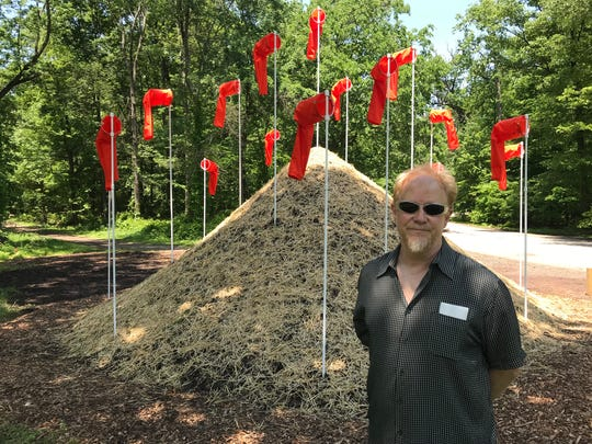 "Greg Leshe, of South Orange, stands in front of his creation, ""Wind Pile"" an installation of 20 wind-socks atop a pile of soil in South Mountain Reservation's Wildflower Sculpture Park on Tuesday, March 29, 2018."