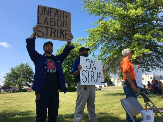 Local AT&T workers hold signs, picketing along Riggin