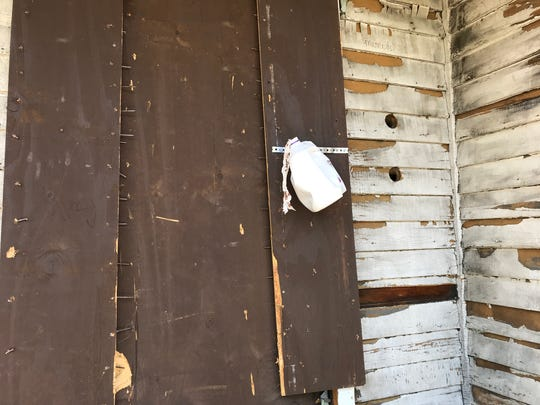 A milk jug serves as a makeshift container for used needles alongside an abandoned house on Ketchum Street.