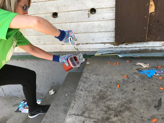 Kara Izzo, a volunteer with Find Your Path, collects used needles behind an abandoned house on Ketchum Street. Every Tuesday, volunteers from Find Your Path walk the neighborhood on North Clinton Avenue in their effort to connect people who use drugs with treatment.