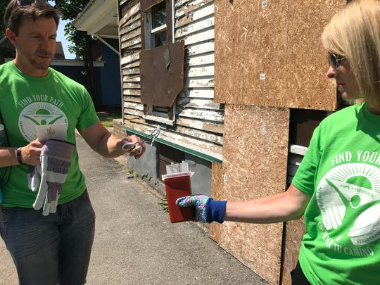 Jonathan Westfall, program director of Find Your Path, drops a used needle into a sharps box carried by volunteer Kara Izzo. Find Your Path links people who use drugs with treatment. Each Tuesday around midday, volunteers walk around the North Clinton Avenue neighborhoods to see if they can find people ready to make a change.