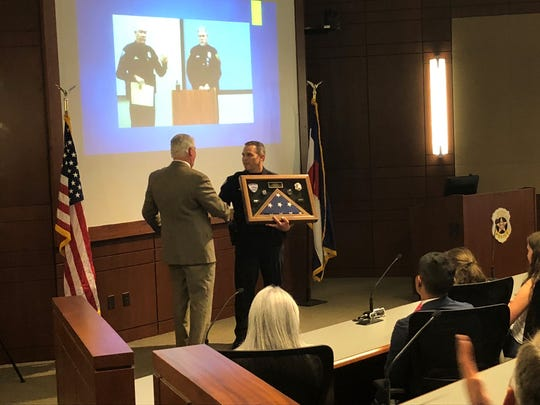 Fort Collins Police Assistant Chief Greg Yeager presents Interim Chief Terry Jones at a ceremony last week with plaque that includes the flag that was hanging during his leadership tenure at the police department.