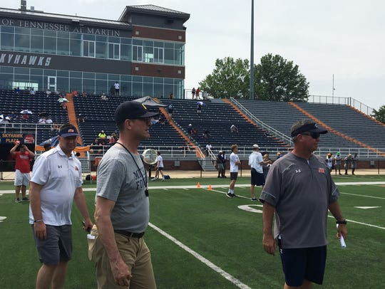 Michigan coach Jim Harbaugh walks with UT Martin coach Jason Simpson during a camp at Martin on Saturday.