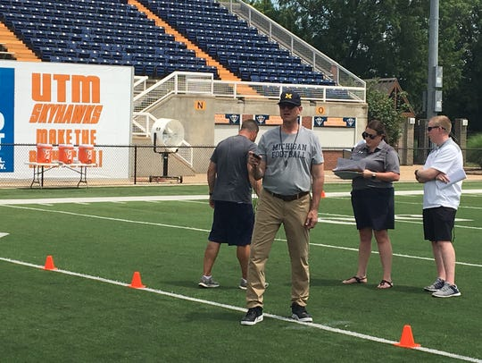 Michigan coach Jim Harbaugh times a 40-yard dash during a camp with UT Martin on Saturday.