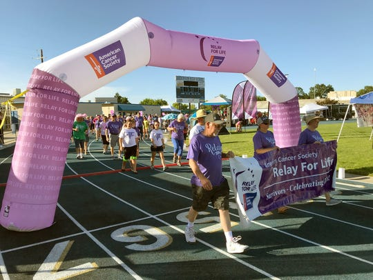 Cancer survivors take their lap Saturday evening at