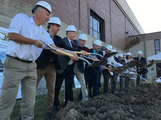 School officials and others break ground Monday on a new entrance, offices and science labs at Delta High School.