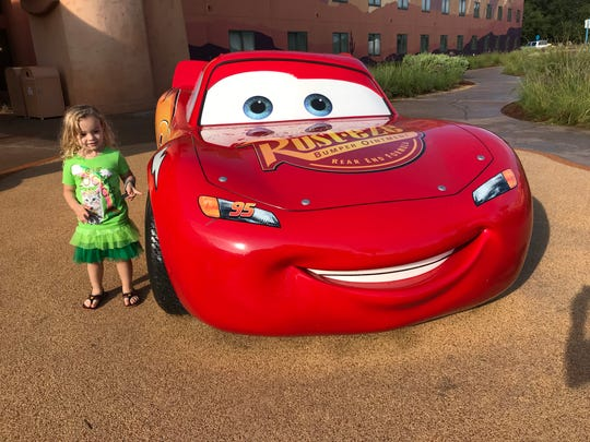Isabella poses by a life-size Lightning McQueen at Disney World's Art of Animation Resort.