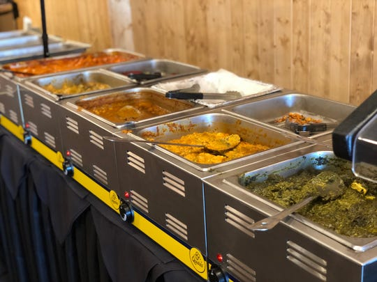 Steamy chafing dishes are filled with rice, meat curries