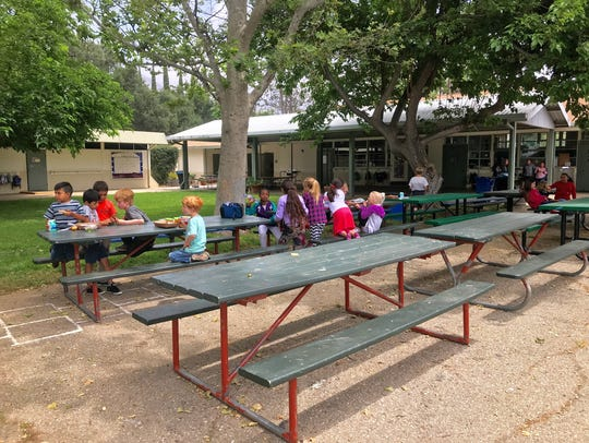 Children eat lunch Wednesday outside Summit School