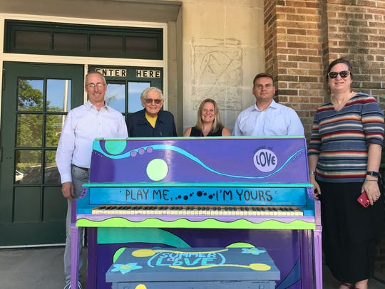 """Cedarburg officials placed a piano in front of the Community Center Gym on June 5 that invites passersby to """"Play me."""" Pictured are (from left) Alderman Jack Arnett, artist Paul Yank, Alderman Kristin Burkart, Parks and Recreation Director Mikko Hilvo and Cedarburg High School art teacher Deb Mortl."""
