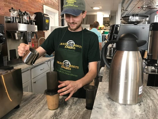 A barista at Grass Roots Xpress makes coffee.