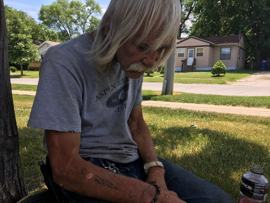 Billy Goossens, a disabled Des Moines man, rests in the shade of a tree near a convenience store where he often draws.
