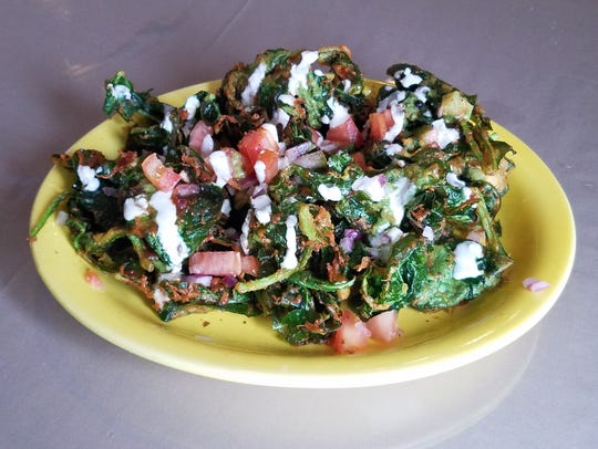 "Palak Chaat means ""spinach snack."" This appetizer consists of fresh spinach leaves dipped in a light chick pea batter and fried, then drizzled with yogurt, tomatoes, and onion."