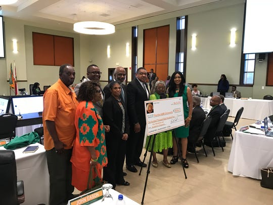 """FAMU National Alumni Association President Lt. Col. Gregory Clark and others present """"check"""" for $600,804 to President Larry Robinson during Thursday's Board of Trustees meeting."""