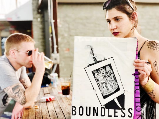 Casey Fang holds up the original Boundless magazine while announcing a partnership with Sugar Mama's for fundraisers, meet-and-greets and Q&As.