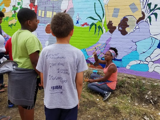 "Tia Richardson coaches volunteers on how to paint details of the ""Sherman Park Rising"" mural, a reaction to a disturbance in the summer of 2016 in the neighborhood. The City of Milwaukee Arts Board named Richardson one of its 2018 Artists of the Year."