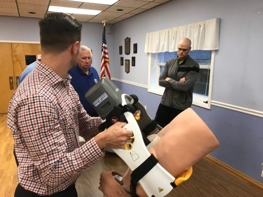 Ryan Pinnix shows Cedar Grove Ambulance and Rescue Squad members that the Lucas CPR machine can help a patient on stairs, unlike manually administered CPR. The training session was held on June 7, 2018.