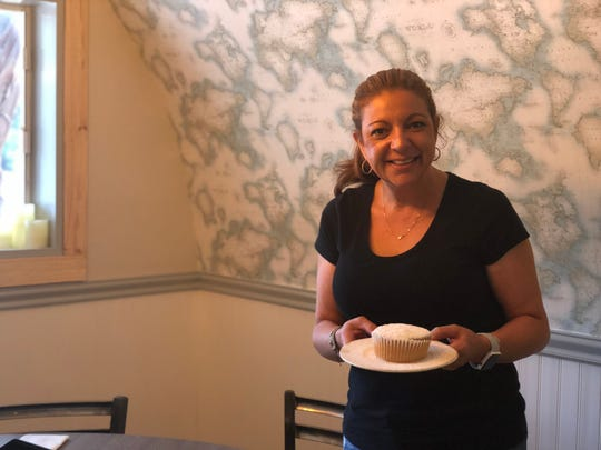 New owner Eve Alves stands in her restaurant with a key lime muffin made by her sister, who also owns a restaurant.