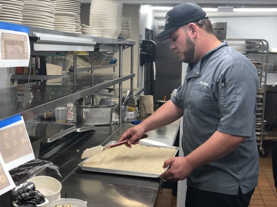 Chef Philipe Schroeder spreads risotto in the newly renovated kitchen.