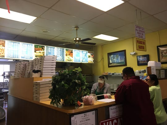 House of Pizza employees take the order of two customers