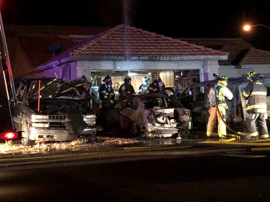 Firefighters investigate the damage after three vehicles