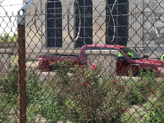 Roses bloom against a Michigan Central Station surrounded by razor wire on June 8. Workers arrived in a Ford F-150 to prepare the site for revitalization.