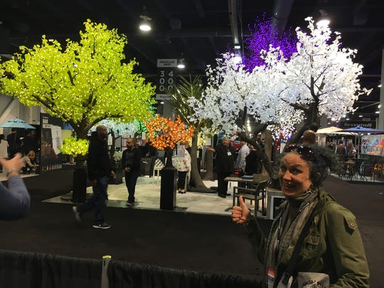 "Bernadette West poses with ""electric forest"" trees. The types of trees will be placed on the roof of Bernadette's Crystal Barrooms, which is scheduled to open in September."