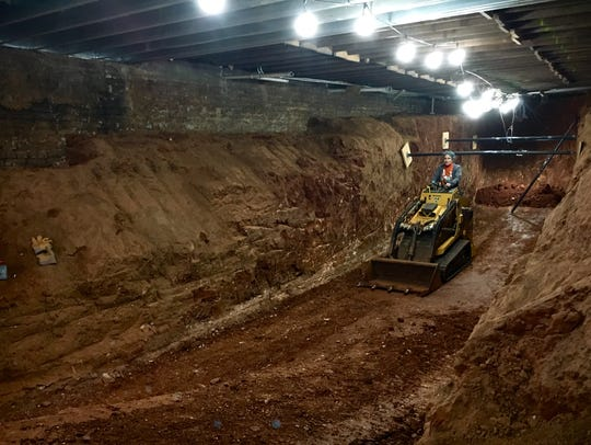 Bernadette West works to excavate the basement at 26