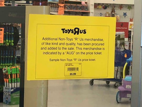 A sign at the front of Toys R Us stores explains how