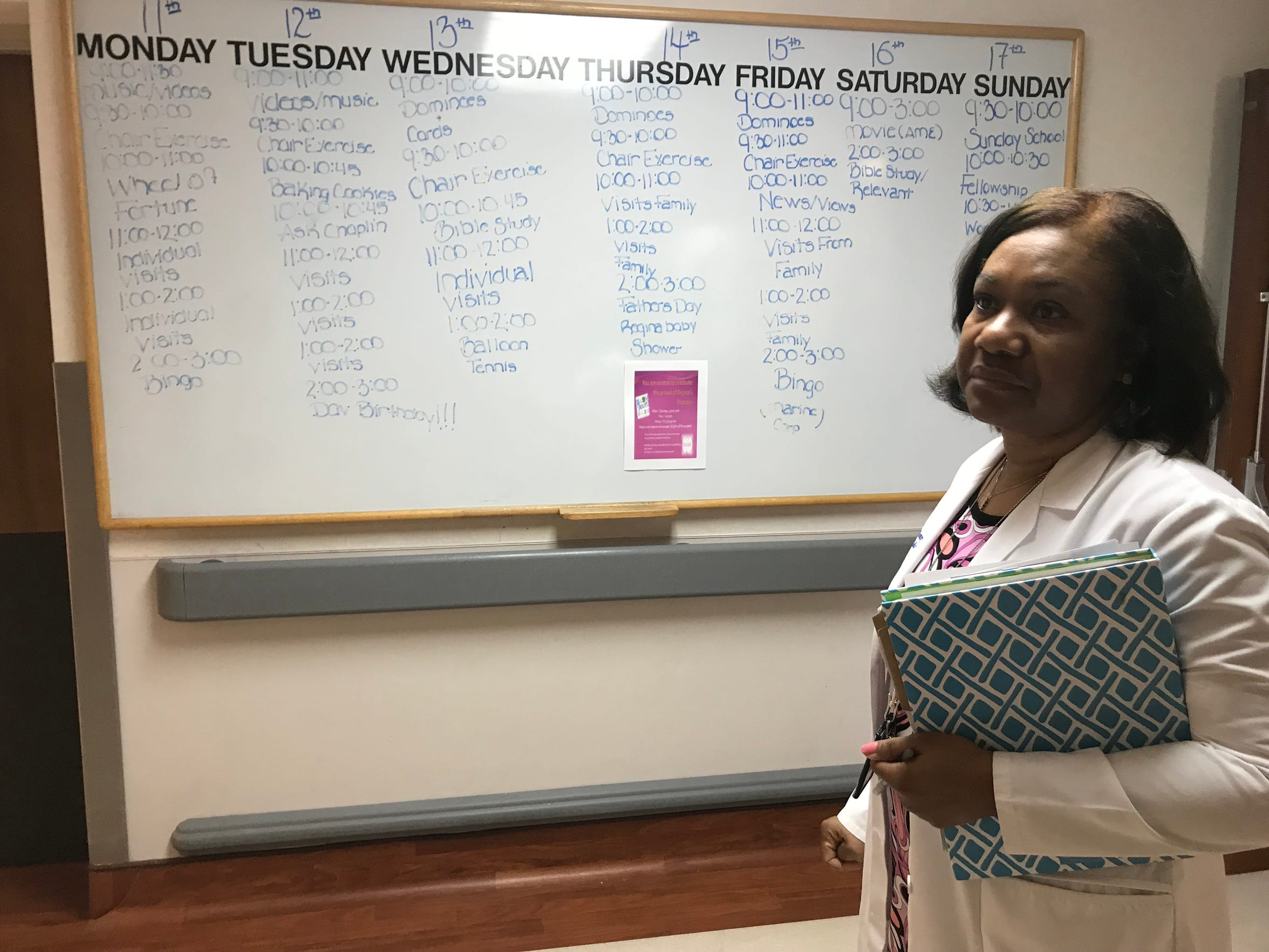 Lisa Bruce with the G.V. (Sonny) Montgomery VA Medical Center walks through the community living center where a large whiteboard displays the residents' schedule. The facility is one of 133 VA-operated nursing homes across the country.