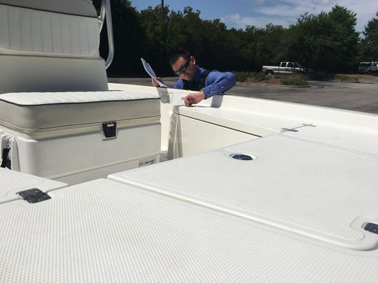 Prattville Police Department Investigator Wesley Clark checks on a boat  in a Prattville business parking lot.