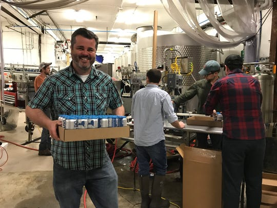 Villa Bellangelo co-owner and winemaker Christopher Missick carries a case of Can Do wines off the canning line.