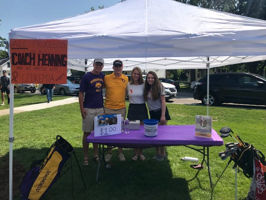 Oconomowoc High School students (from left) Matt McKain, Travis Cooke, Madison LaPaz and Lauren Alioto sell ice cream at the Oconomowoc baseball sectional on June 5 to raise money for boys golf coach Bruce Henning, who was diagnosed with leukemia.