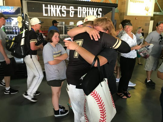 Evan Etchison and Beth Etchison hug after Daleville