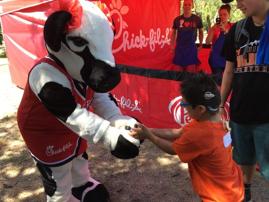 Konner Kasner accepts a souvenir from Chick-fil-A's Little Cow during the 41st annual Rehab Camp.