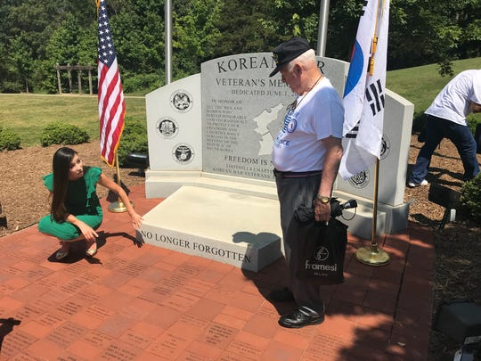 Korean War veterans advocate Hannah Kim examines the war monument at Conestee Park.