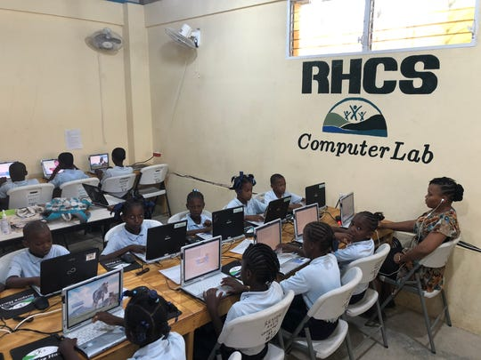 Students at the Respire Haiti school work on laptop computers.