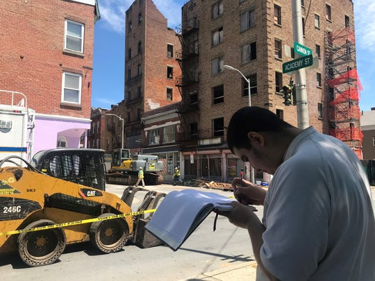 Jaime Vivero Castonda, 16, stands on the corner of Academy and Cannon streets to draw the buildings near 19 Academy Street. He said he wants to have a memory of them before the City of Poughkeepsie demolishes them.