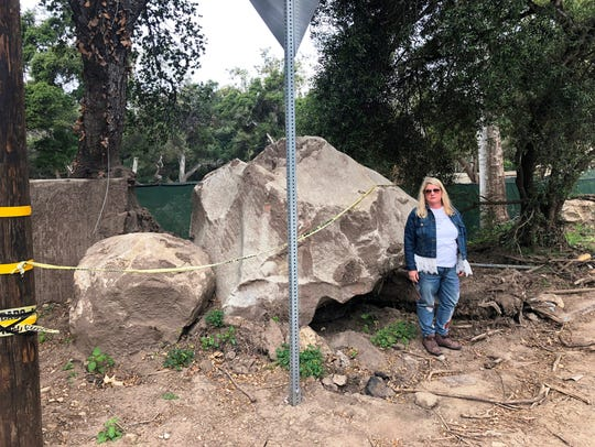 Kim Cantin stands next to a boulder near what is left