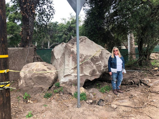 Kim Cantin stands next to a boulder near what is left of her home in Montecito, California. Cantin, who lived in Mason before moving to California, lost her husband and 17-year-old son in the devastating January mudslides.