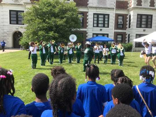 Students from Nolan Elementary-Middle School watch as the Cass Technical High School band performs after a news conference at the school Thursday.