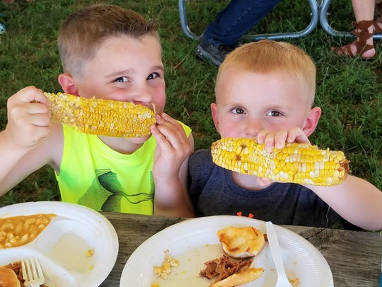 Blake Eickhoff, 6, and Mason Eikhoff, 4, tear into ears of smoked corn from Miller's BBQ at the Franklin St. Bazaar.