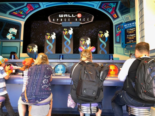 Disneyland goers play Wall-E's Space Race on June 21, 2018, a new game at Pixar Pier in California Adventure.